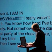 man sitting at a laptop onstage