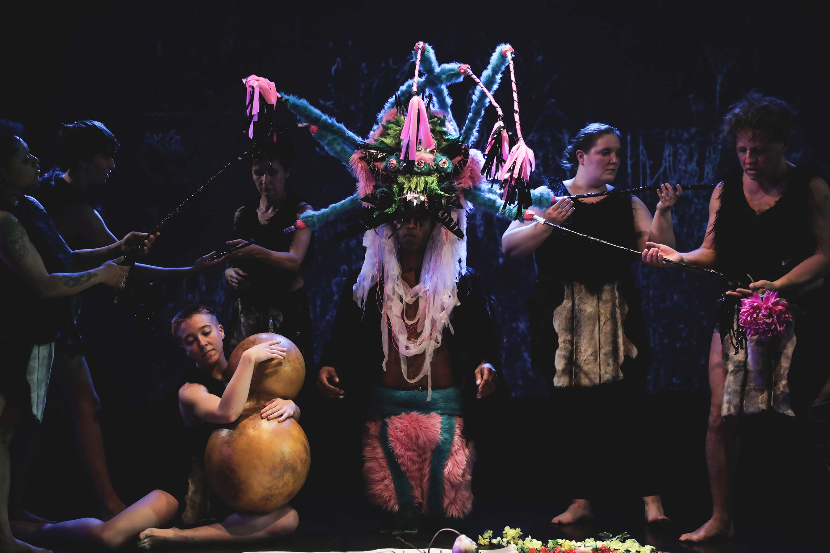 persona wearing a colorful headpiece standing onstage surrounded by other performers