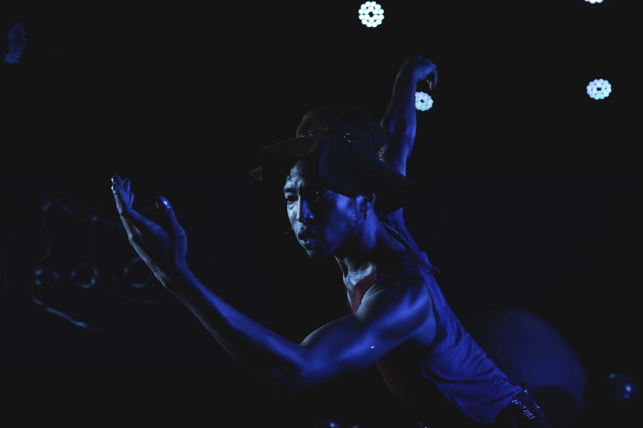 person dancing lit by blue light