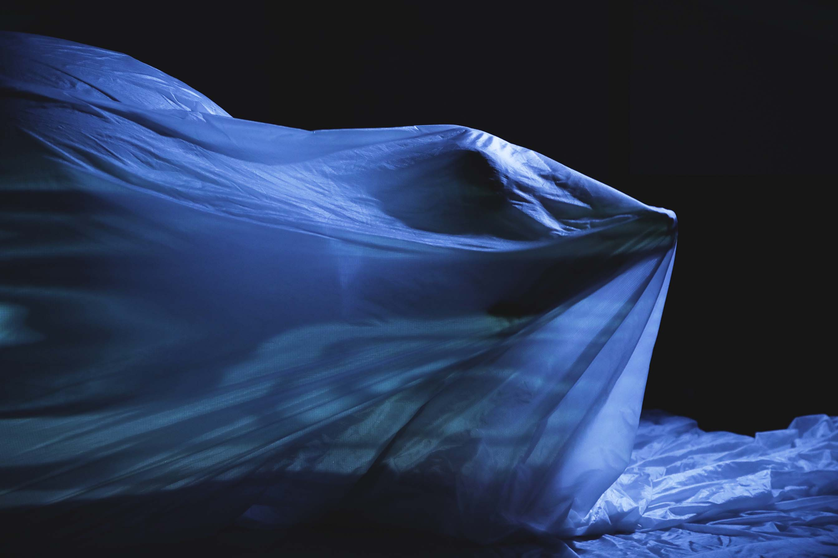 person moving under a white sheet
