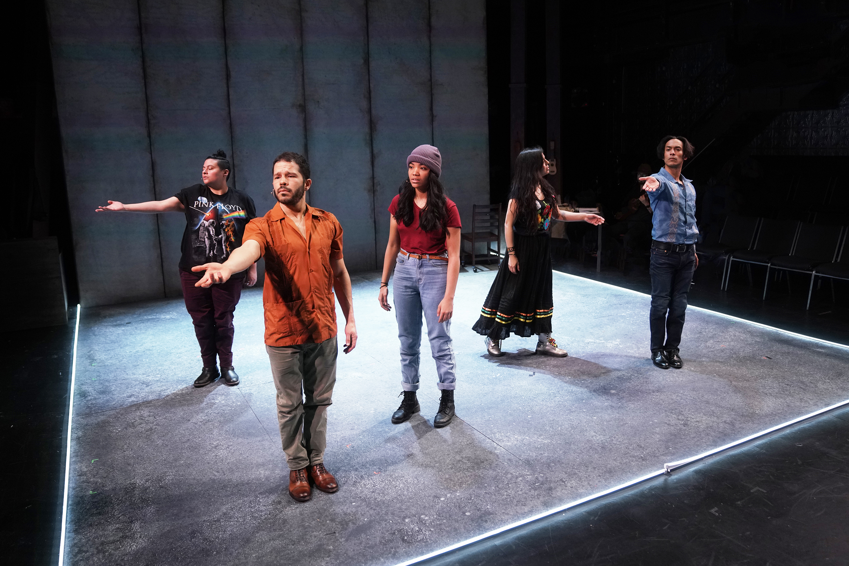 five performers onstage with outstretched hands