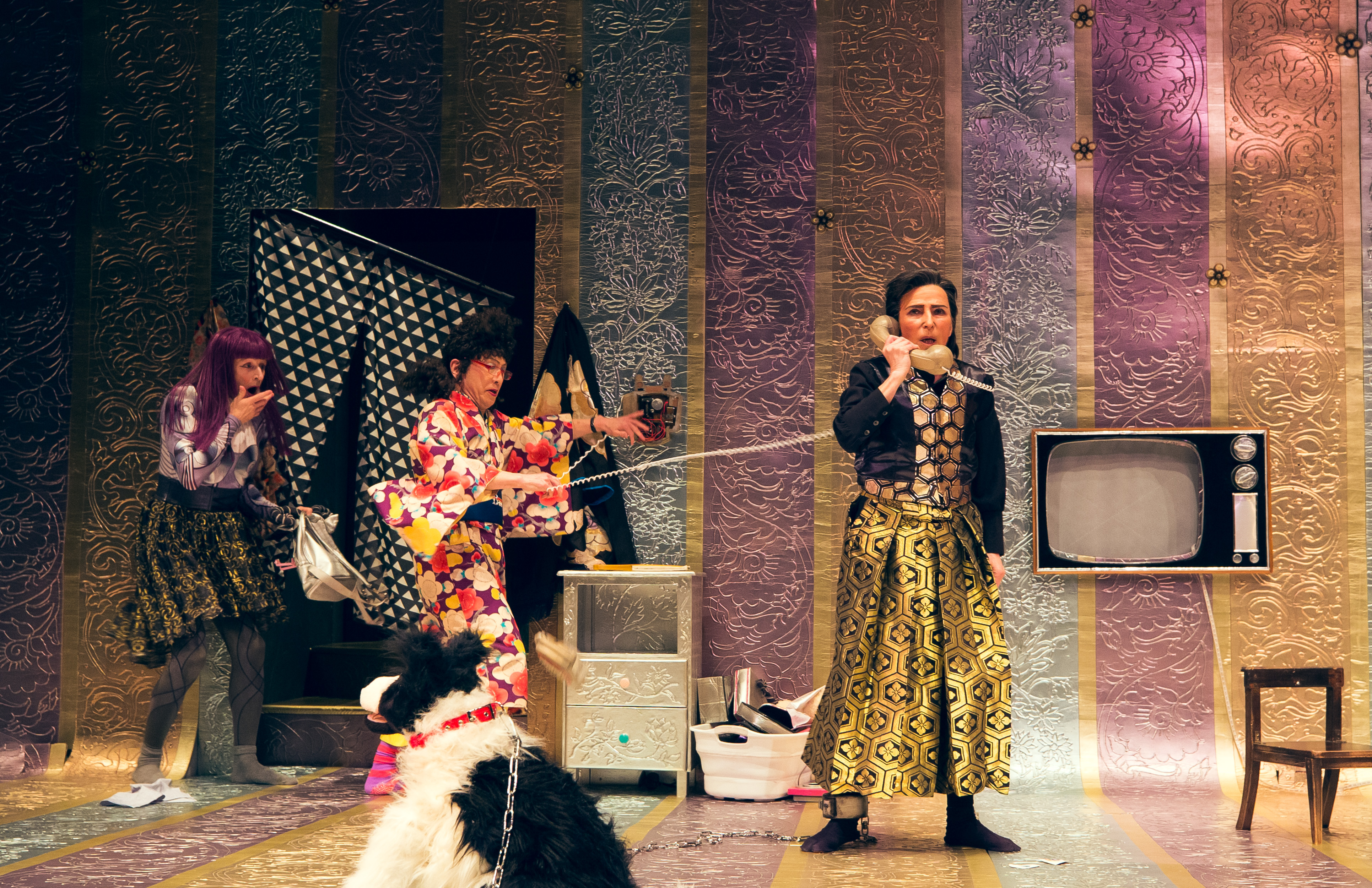three performers onstage, one is on the phone
