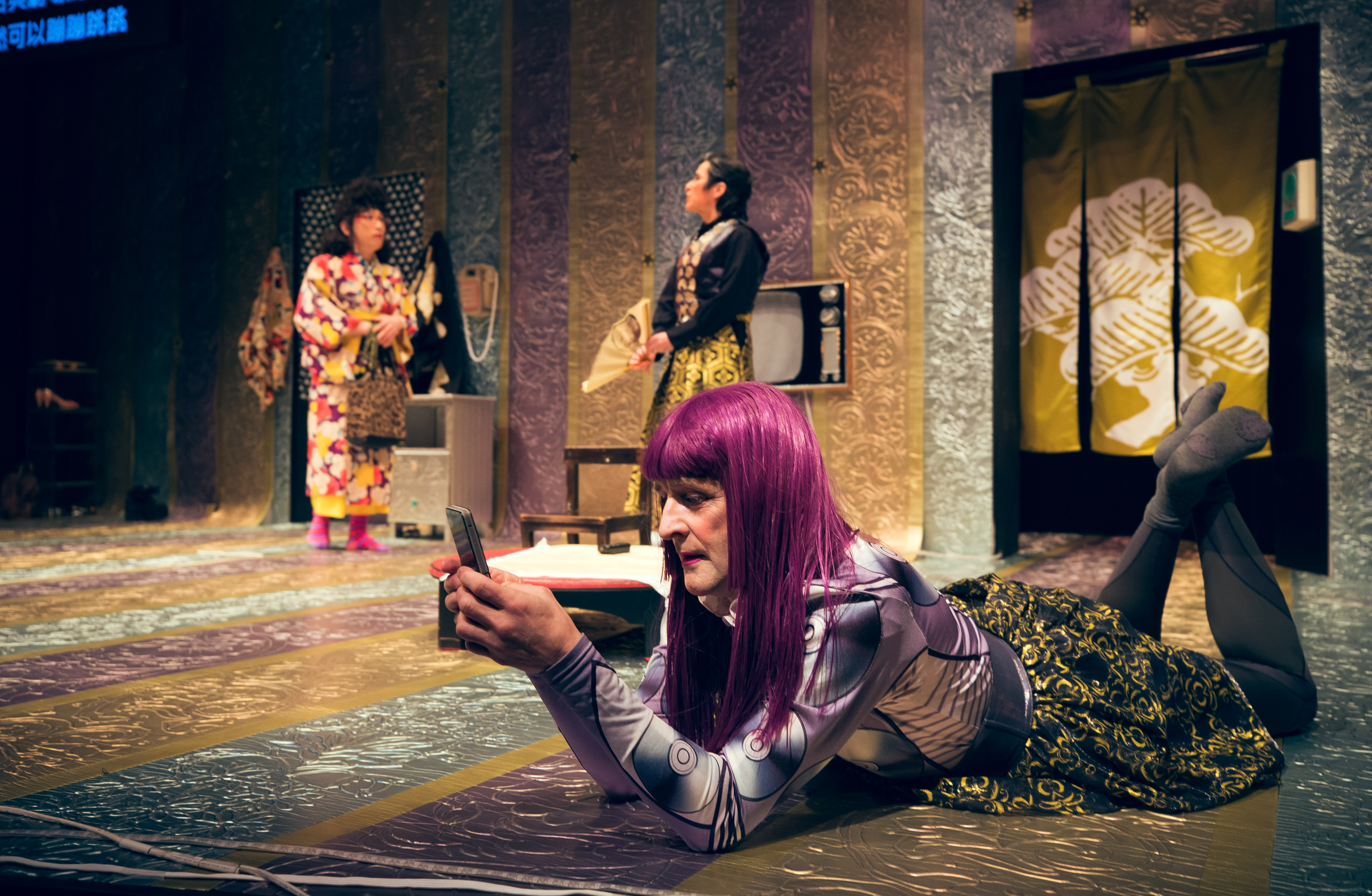 a performer in a purple wig lays on their stomach looking at a cell phone