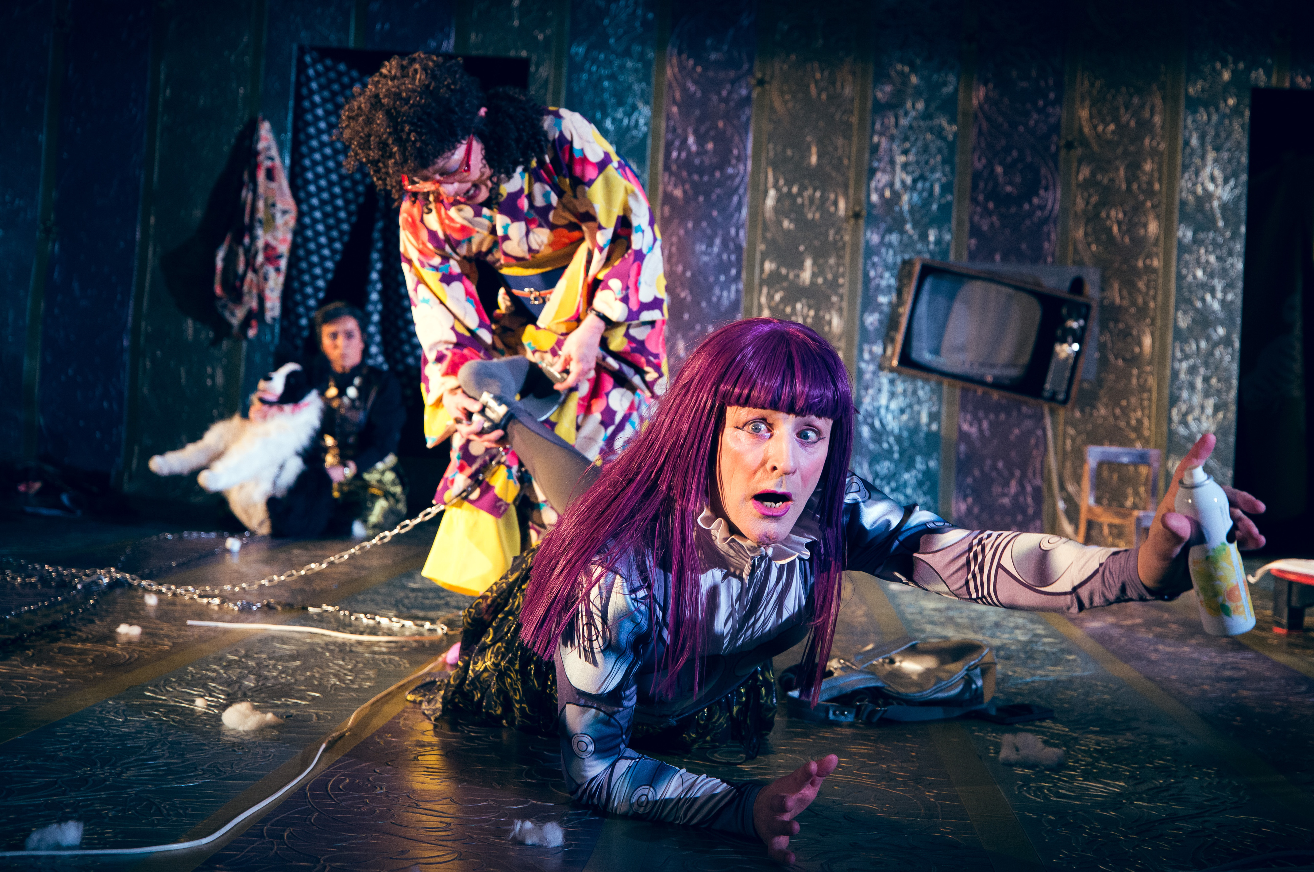 a performer in a purple wig in crawling toward the camera