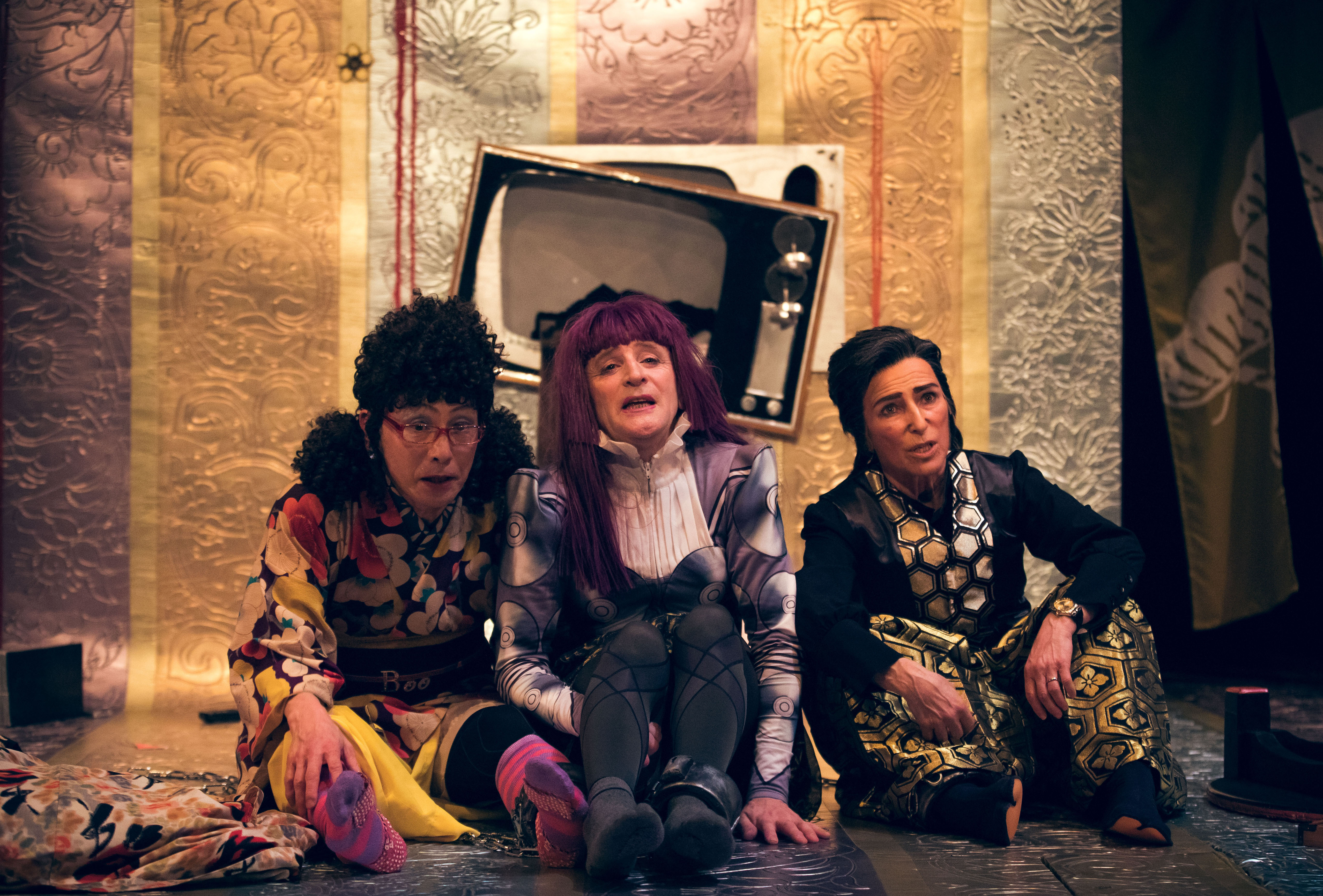 three performers sit in front of a broken tv