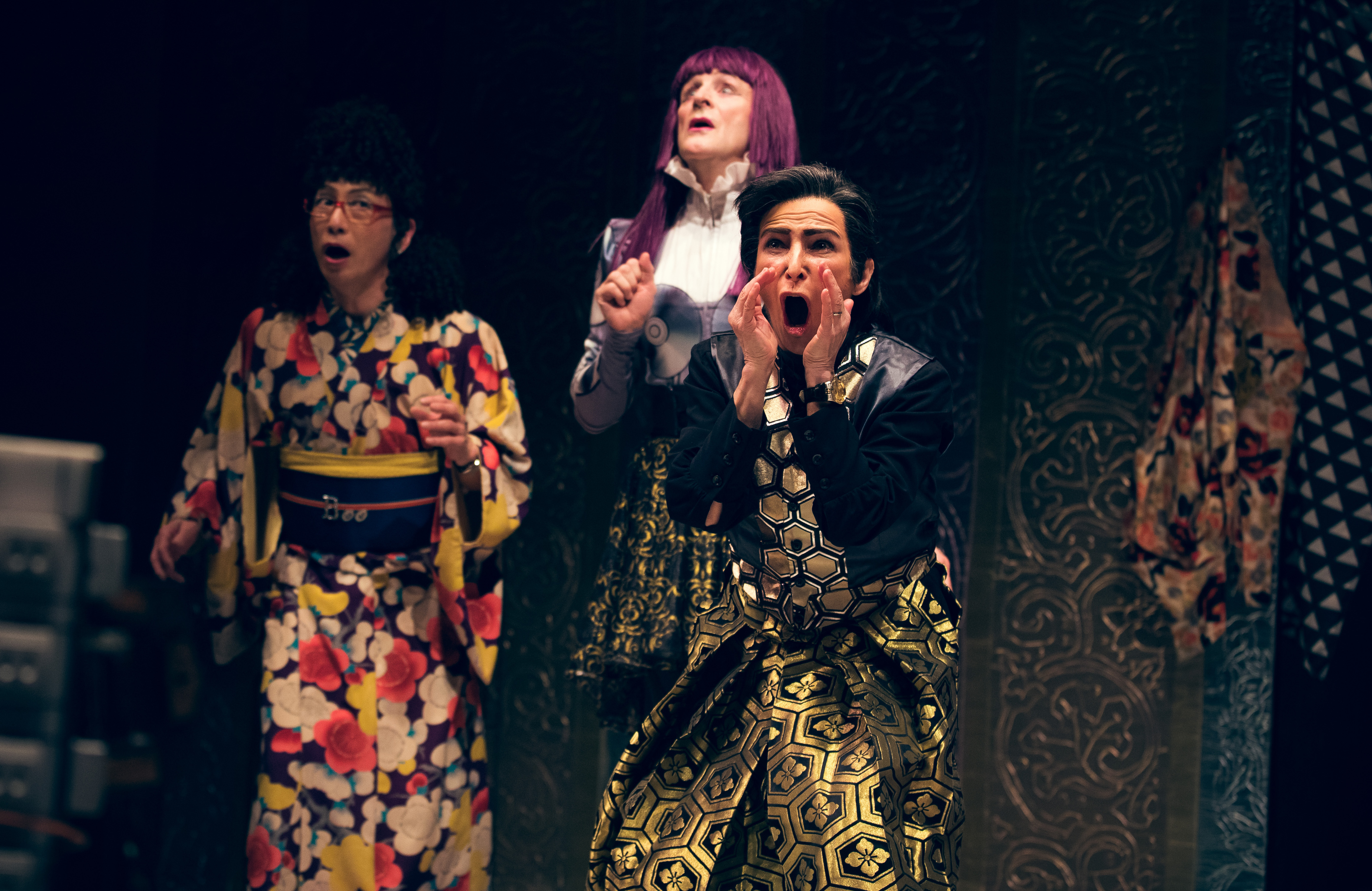 three performers onstage. two are shouting.