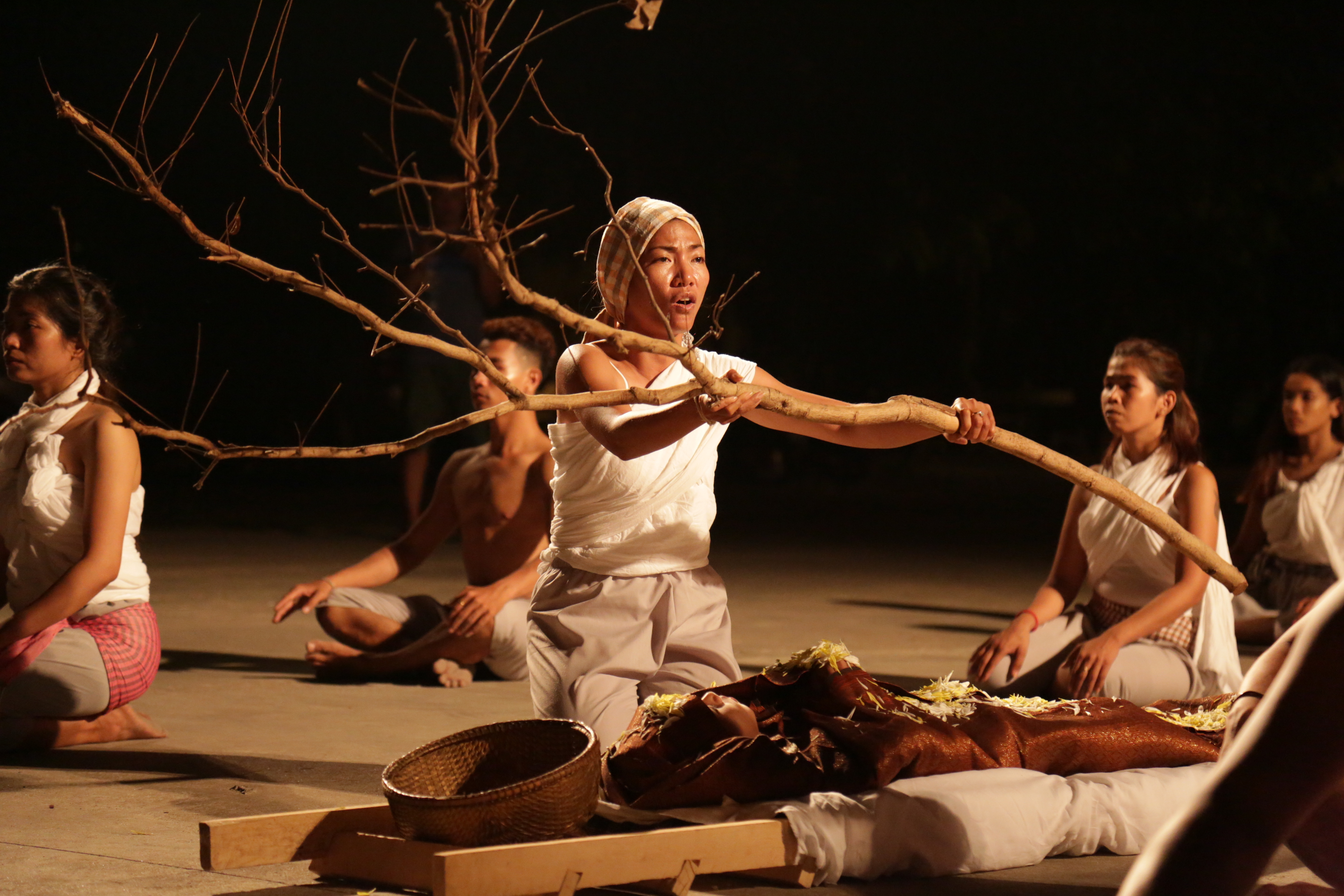 a performer wearing white holding a large tree branch