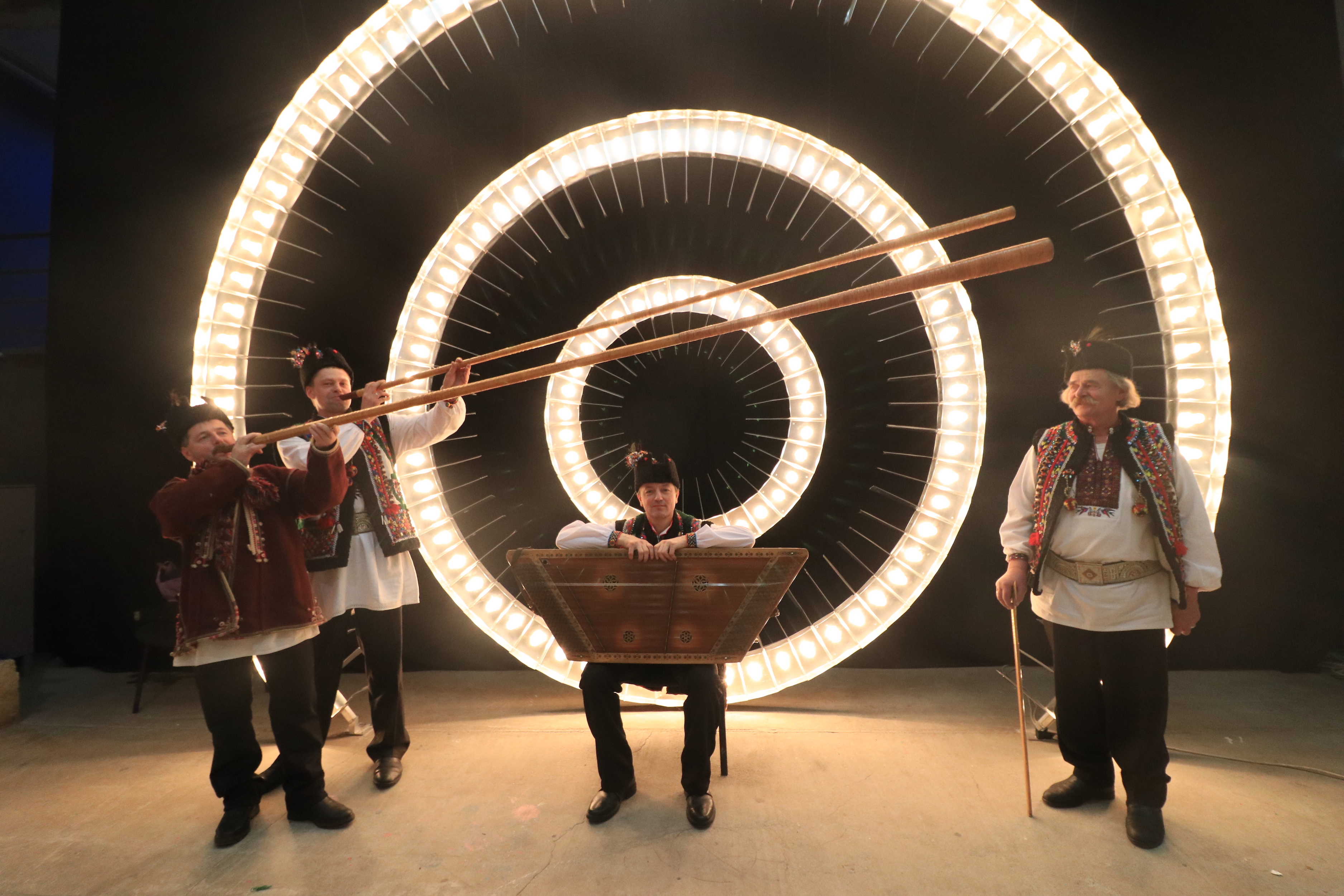 four performers onstage in front of lights. three are holding instruments.