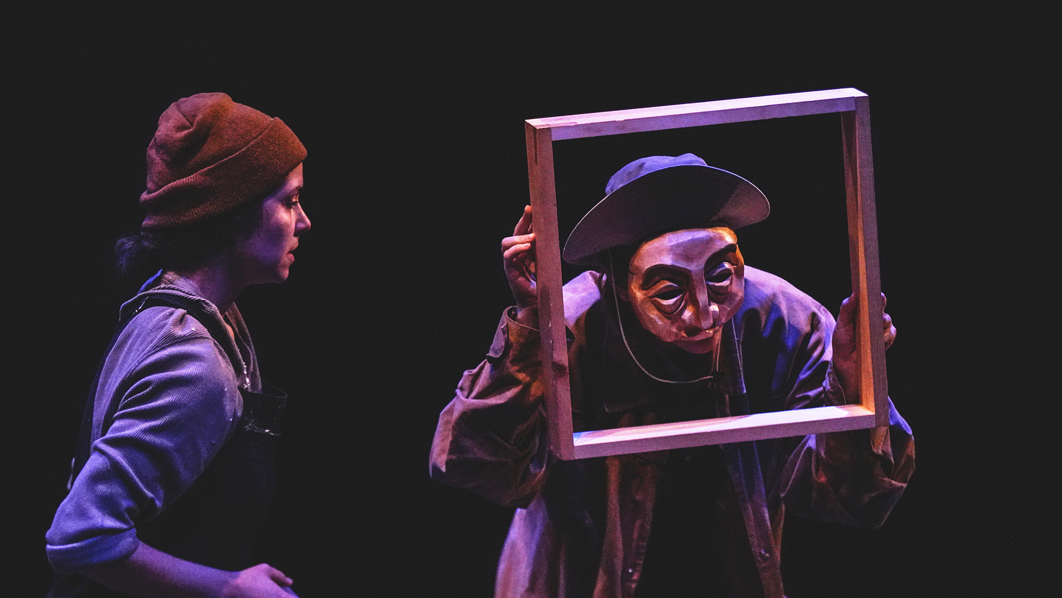 two performers onstage light by purple light. one performer is holding an empty picture frame.