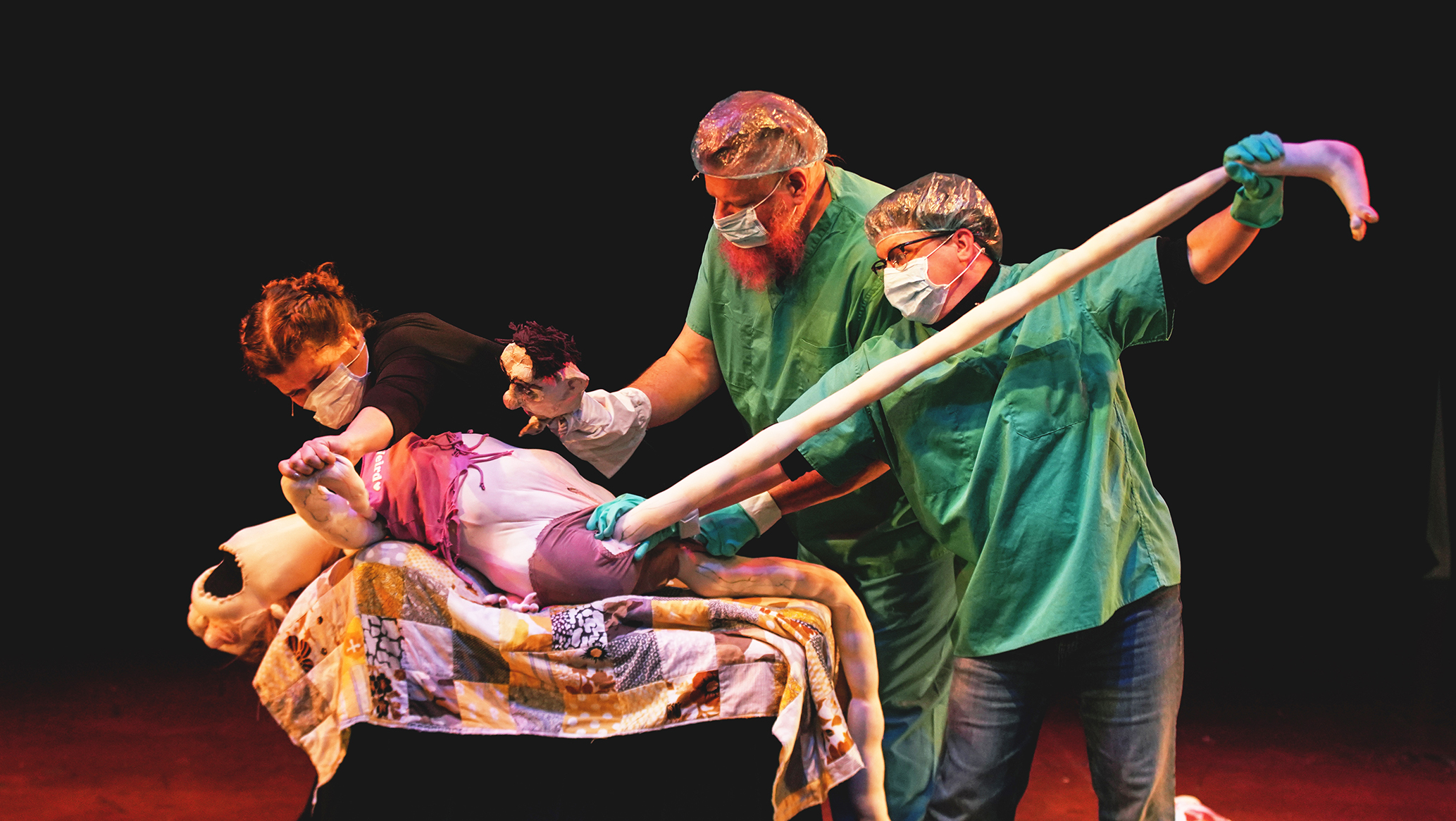 three performers surround a puppet