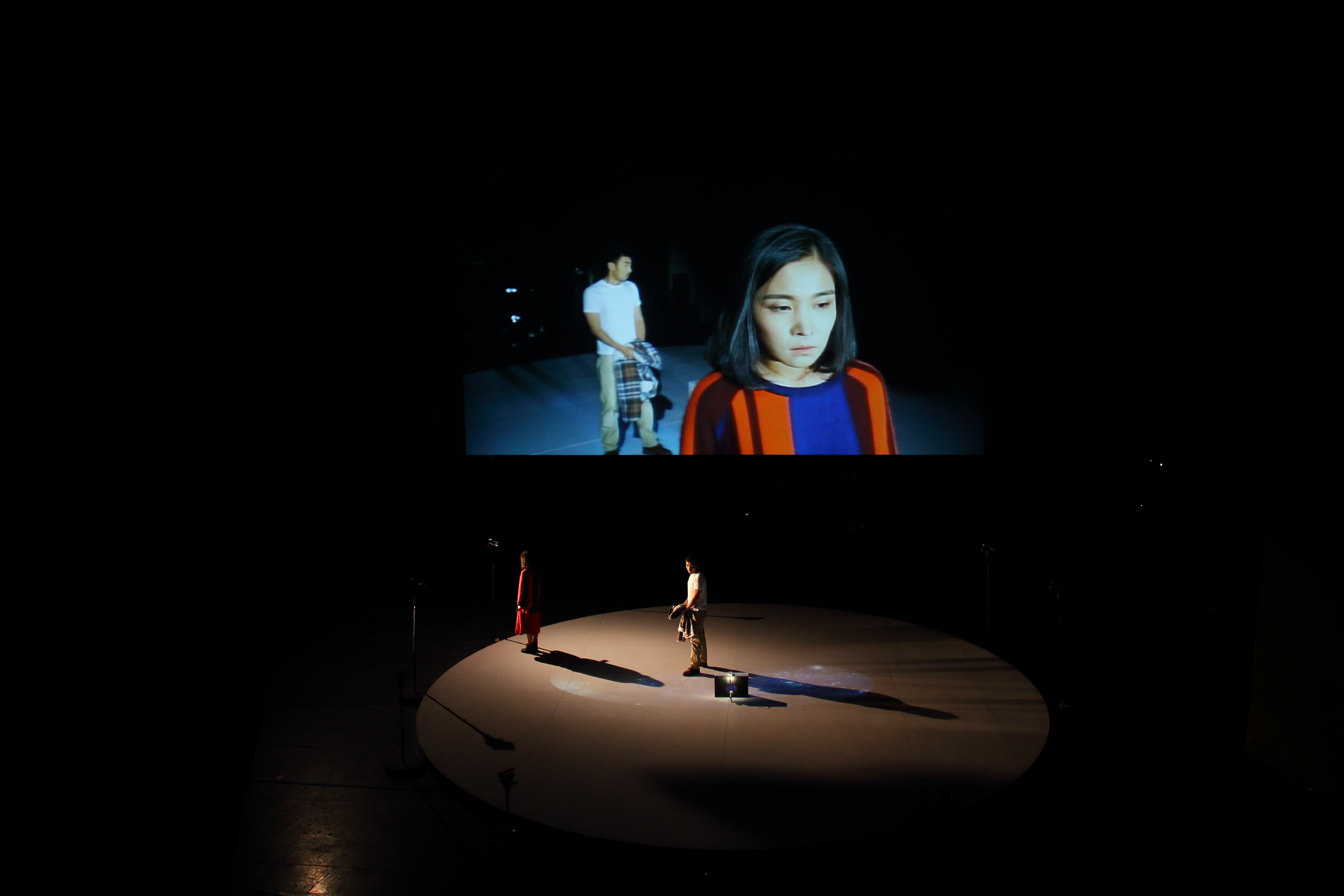 two performers onstage, their image reflected on projection above