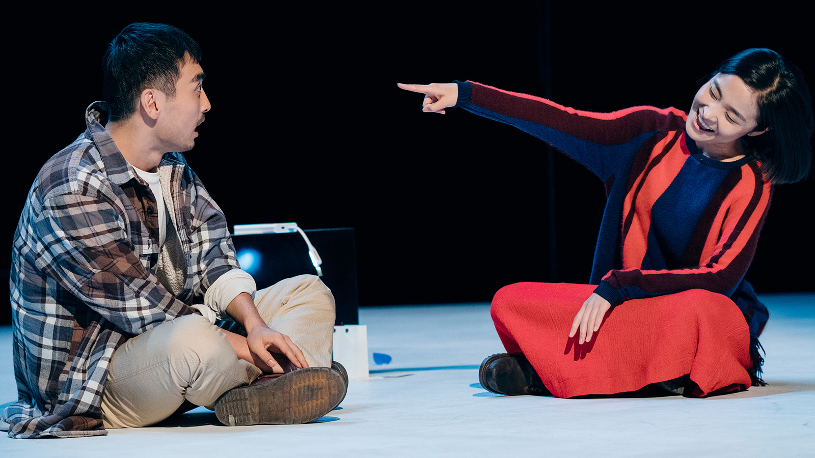 two performers onstage, one pointing at the other.