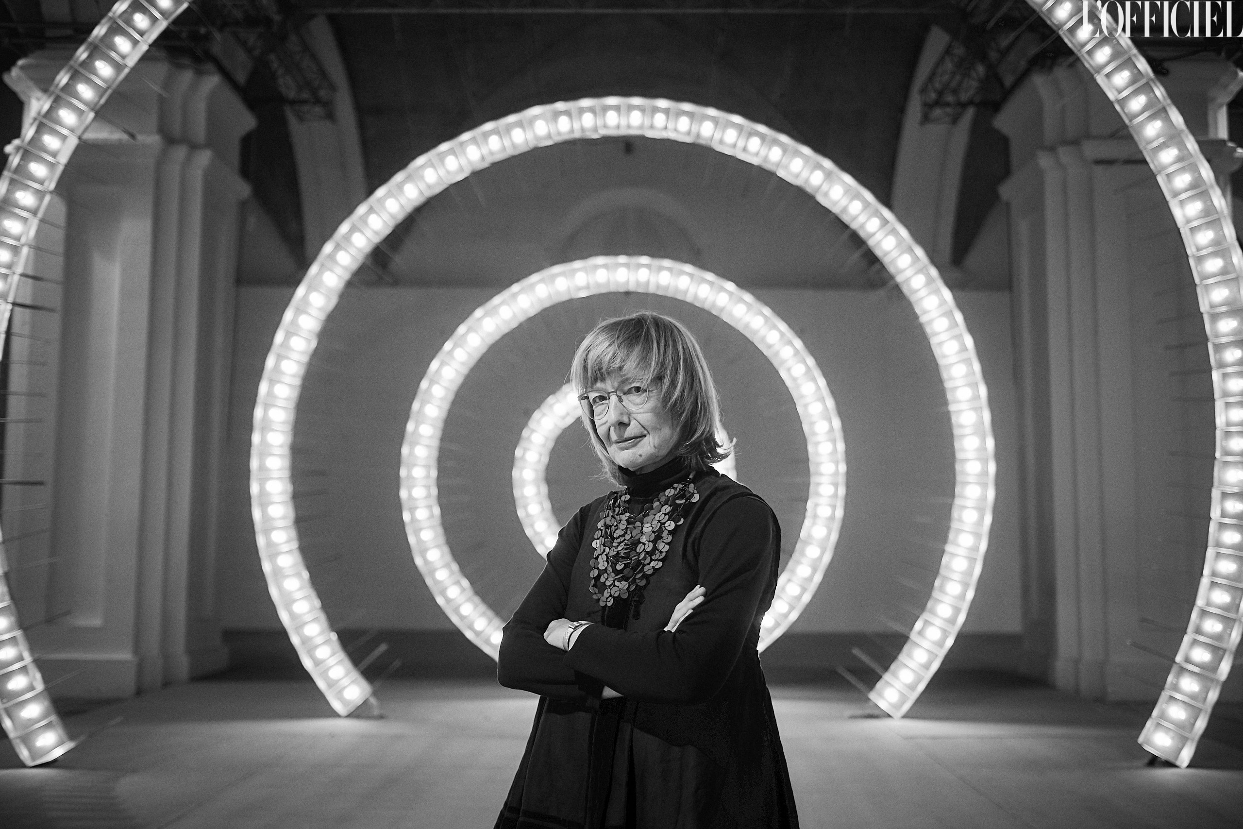 black and white photo of a woman standing in front of circular light fixtures