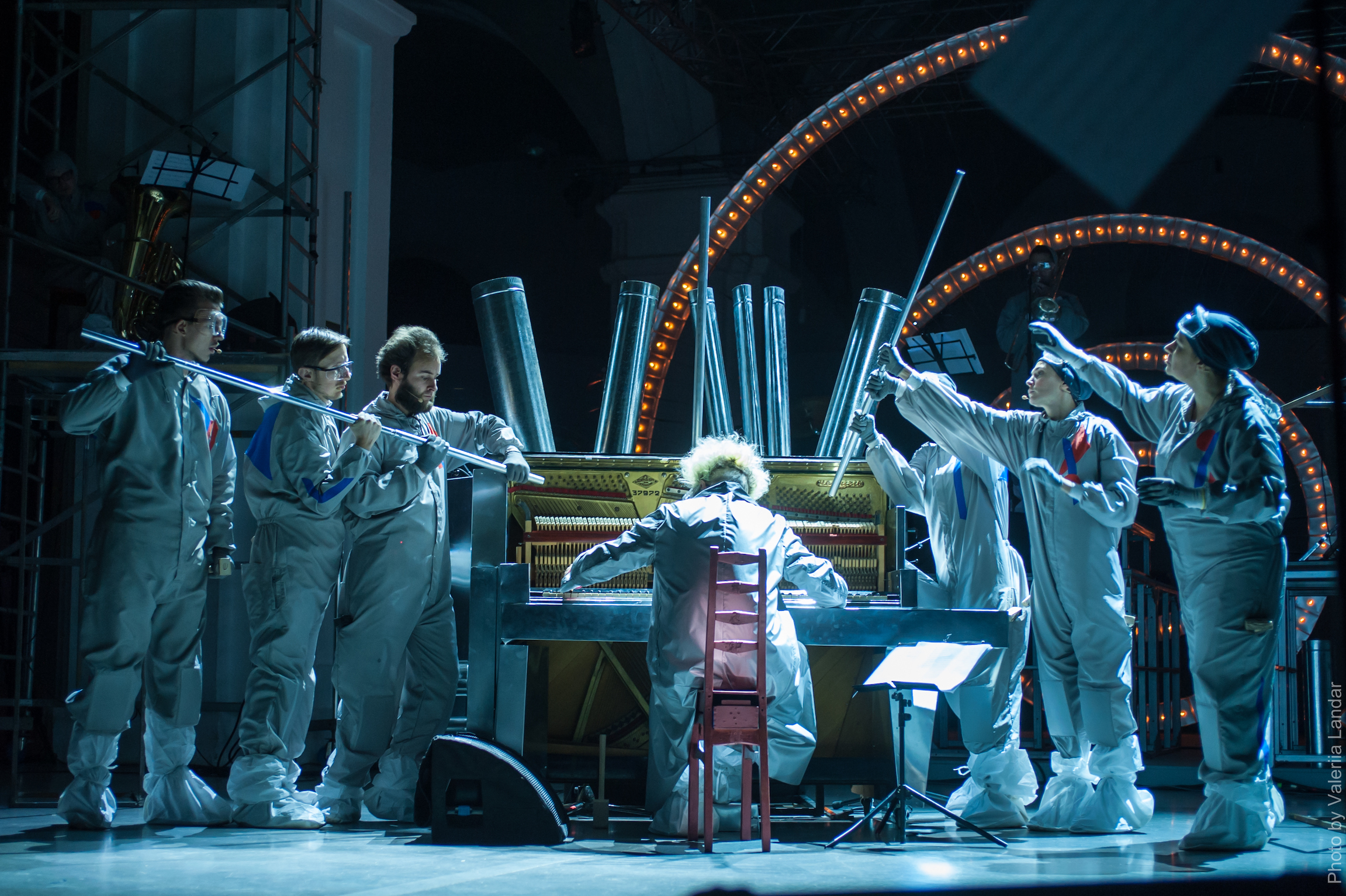 a performer sits at a piano onstage, other performers stand on either side of the piano.