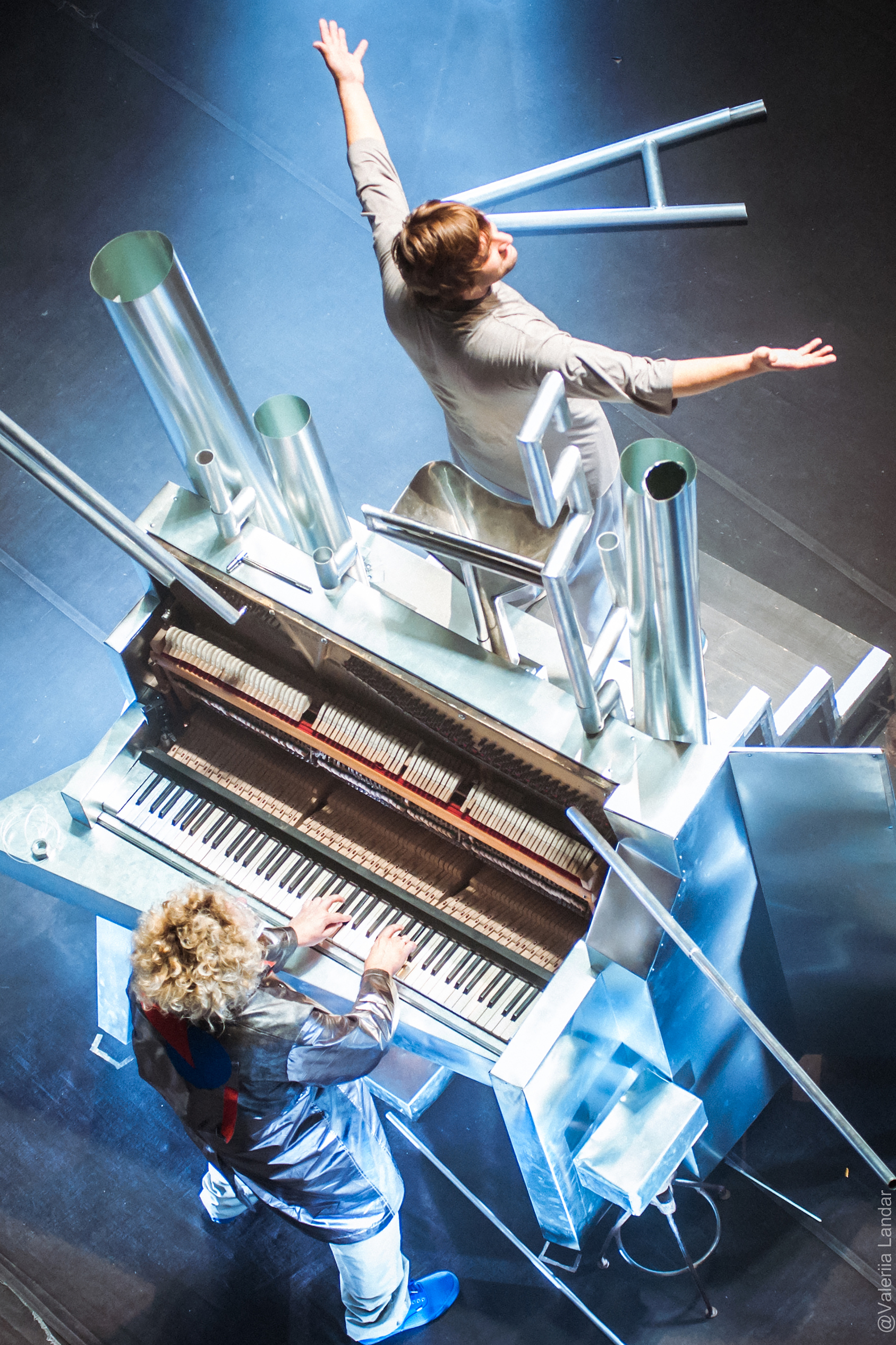 one performer sitting at a piano, another stands on top