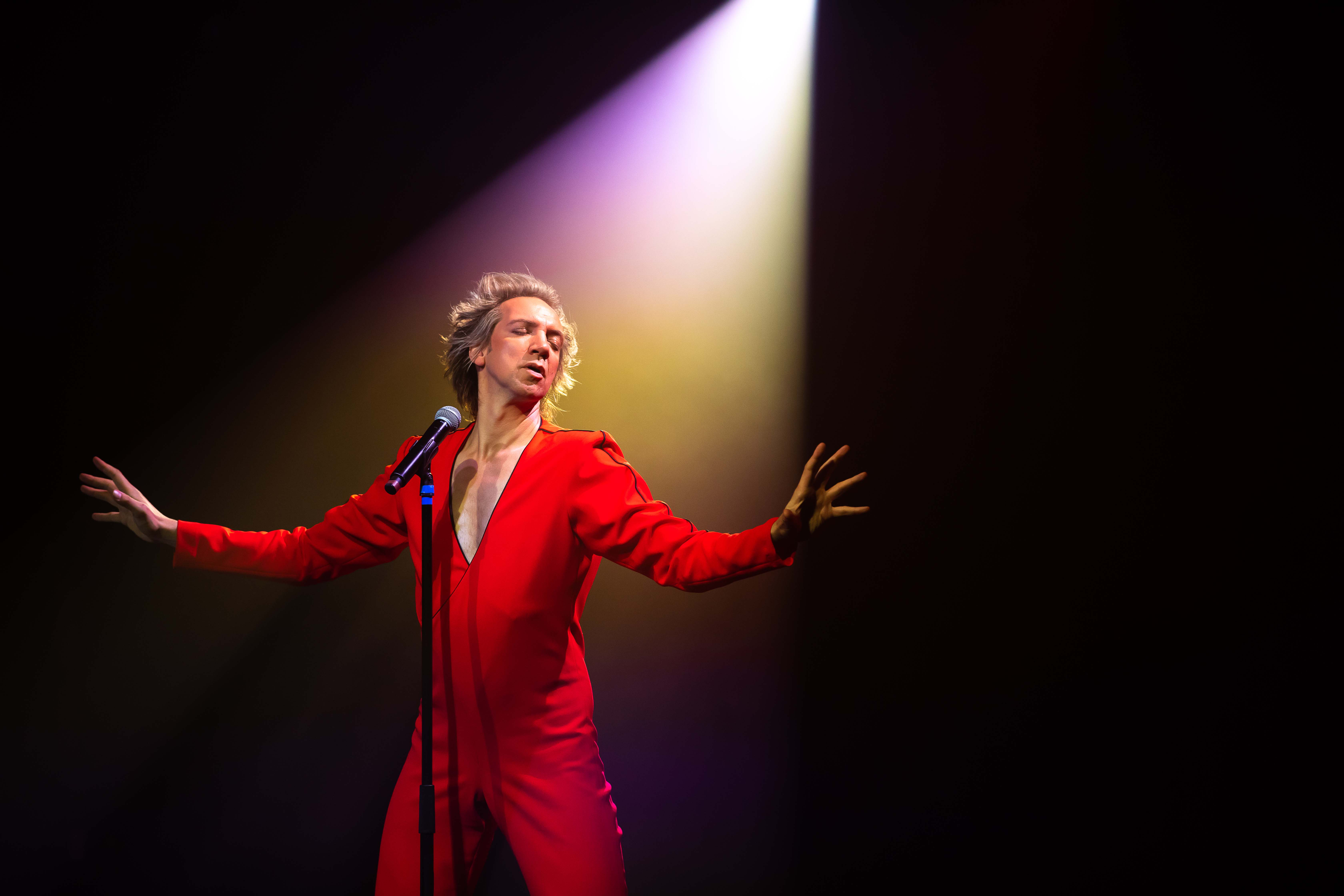 a performer wearing red standing in a spotlight