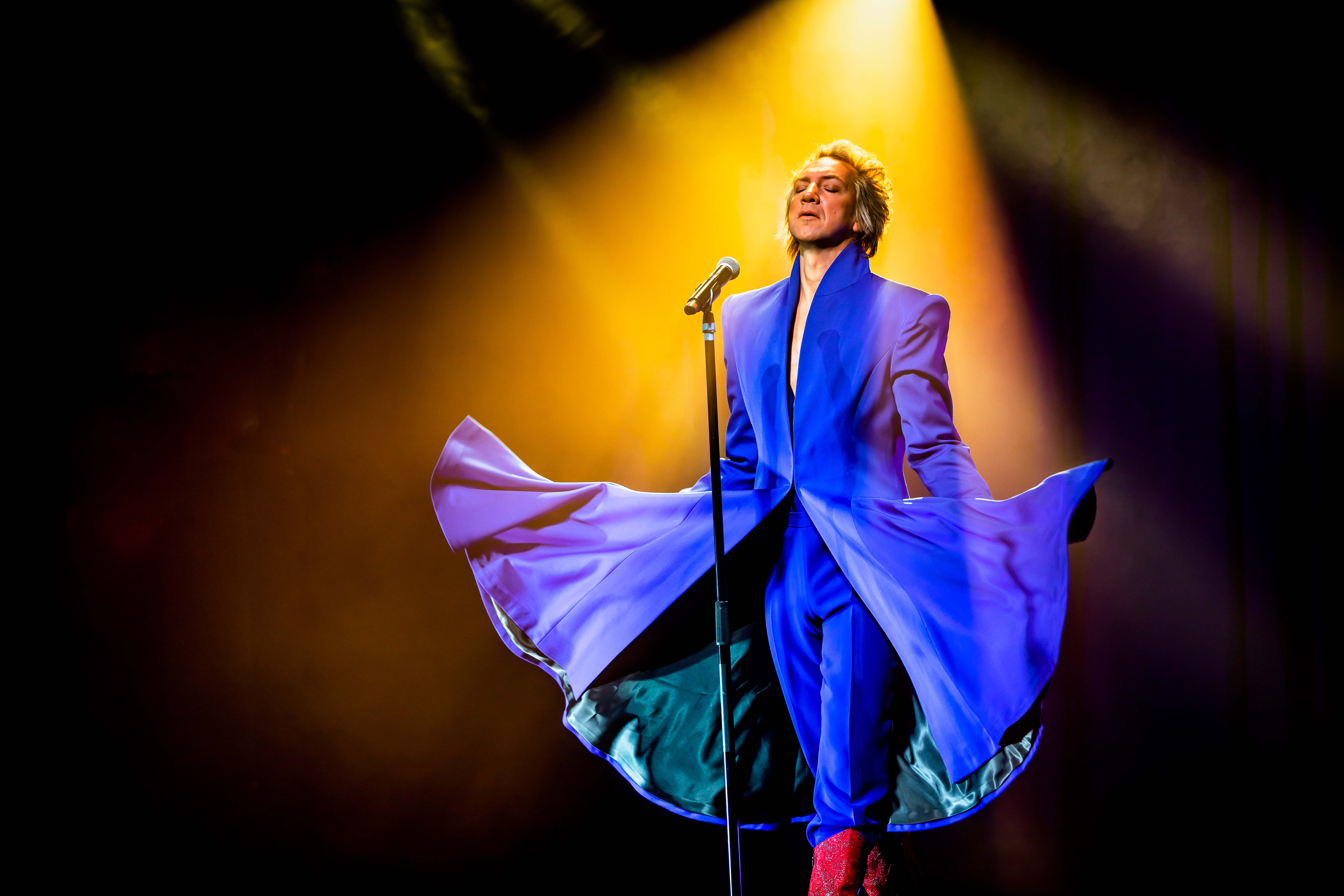 a performer wearing blue standing in a spotlight
