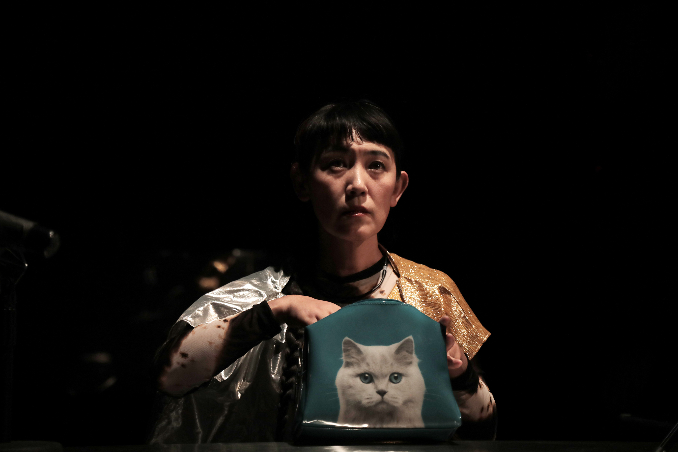 a woman holding a bag with a cat on it