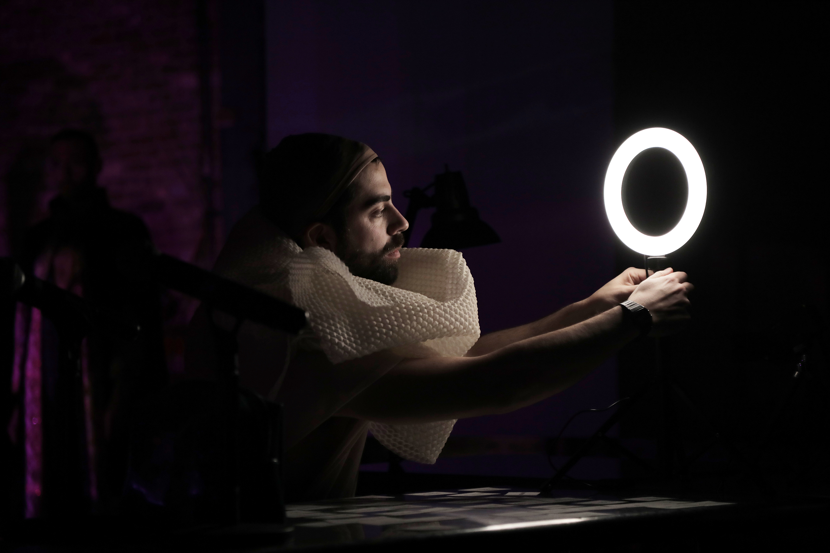 man looking into a ring light