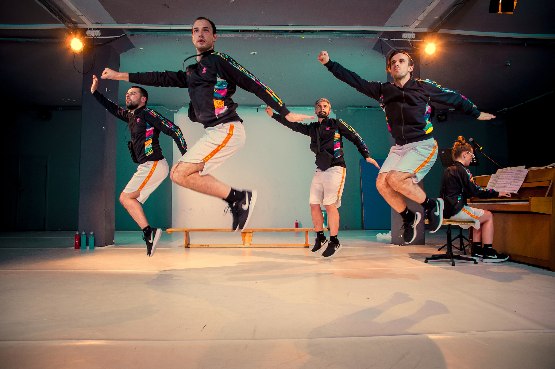 four performers jumping in the air