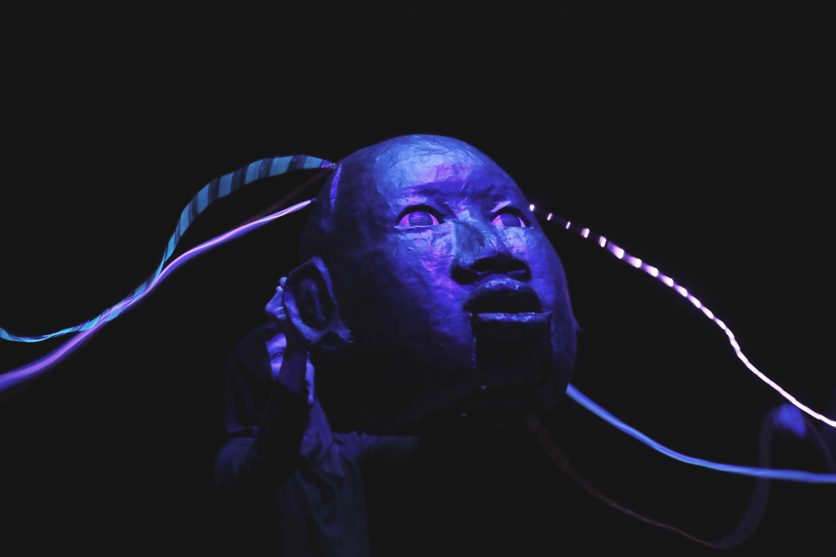 a blue face with wires coming out of the head