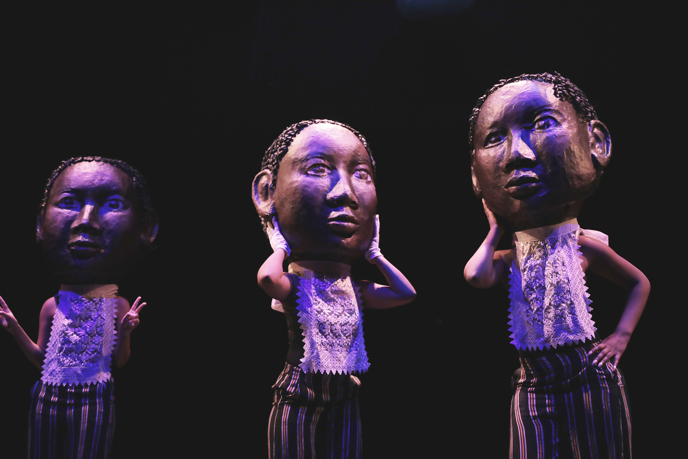 three performers wearing large puppet heads