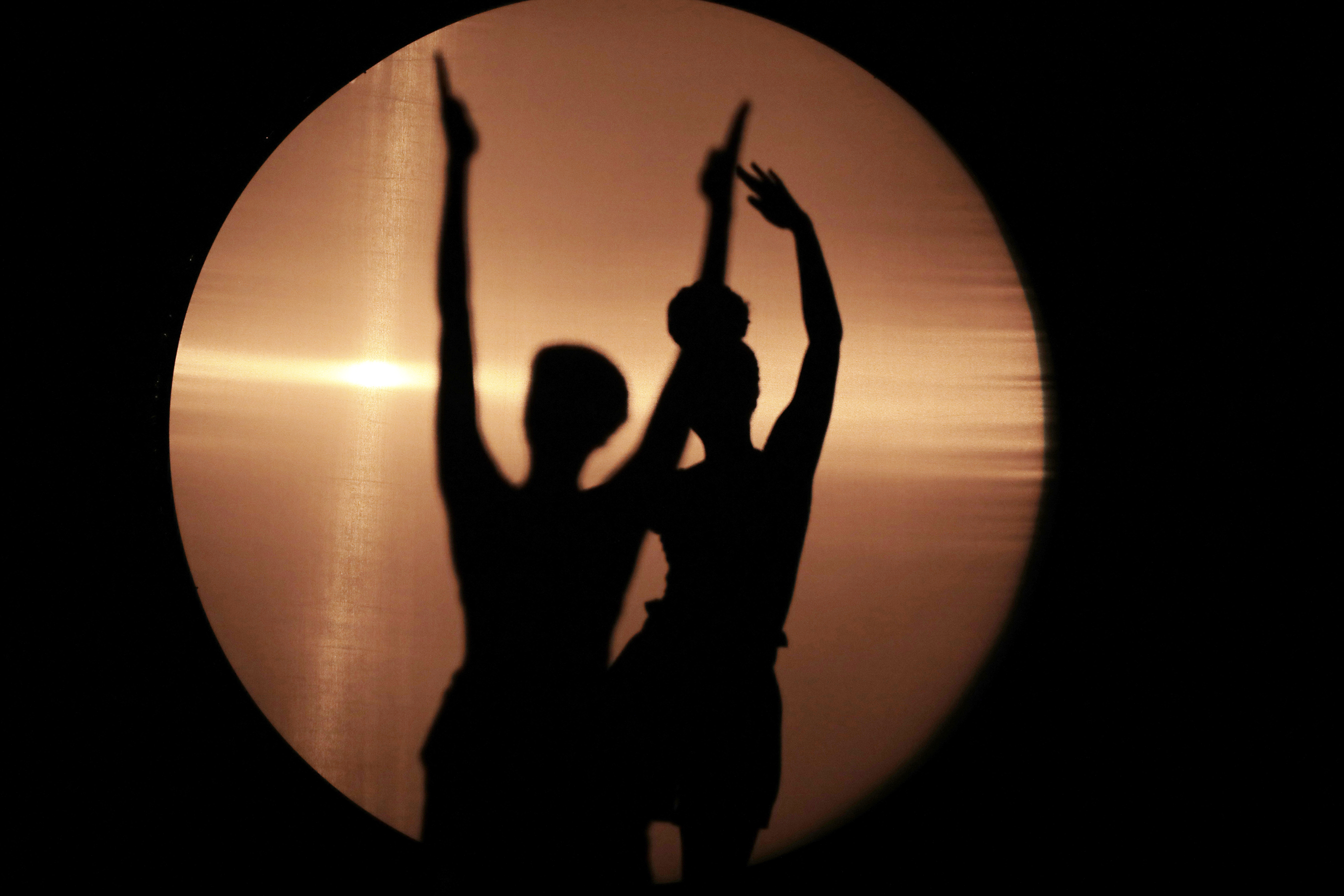silhouette of two dancer in front of a light