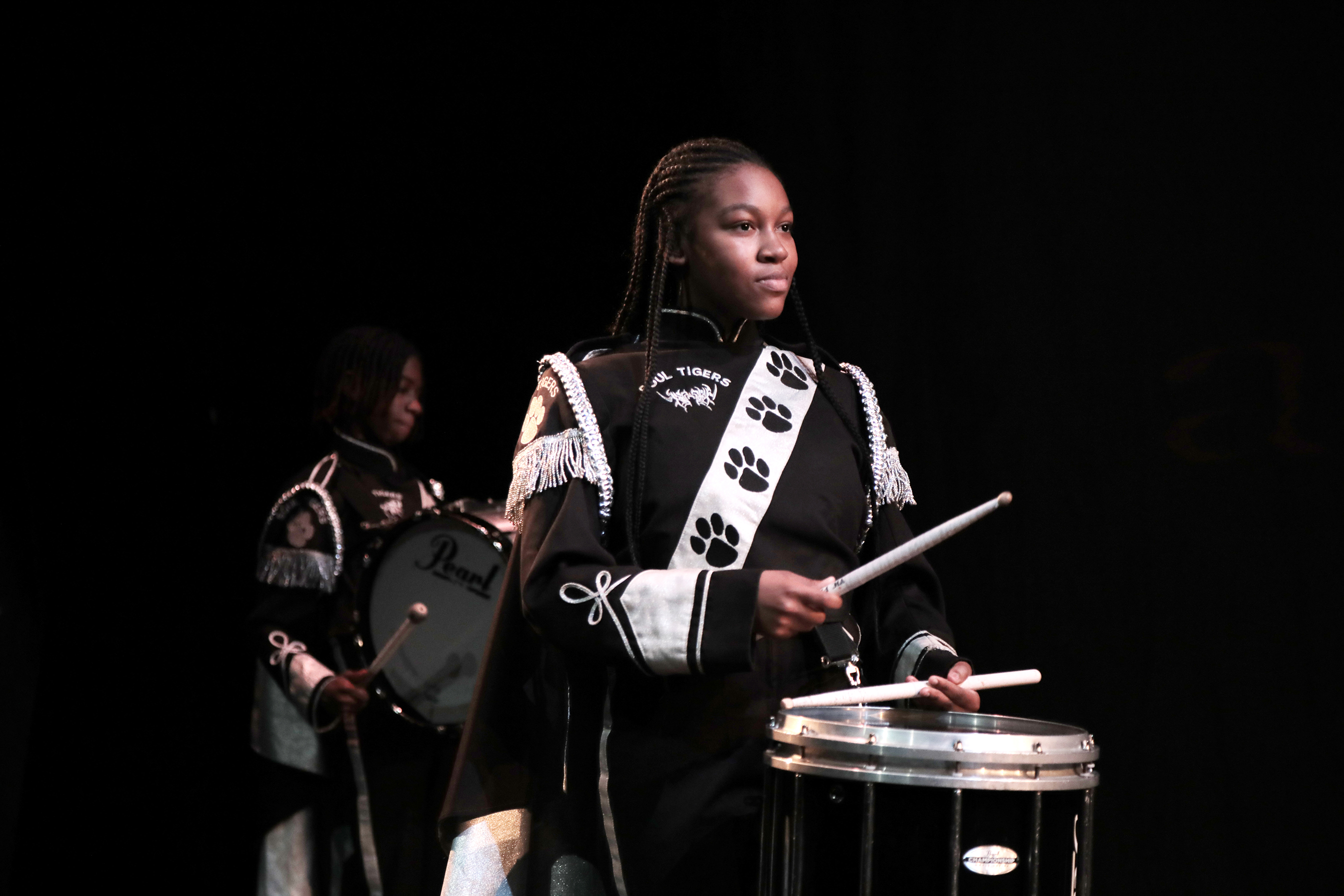 performer in a band uniform holding a drum