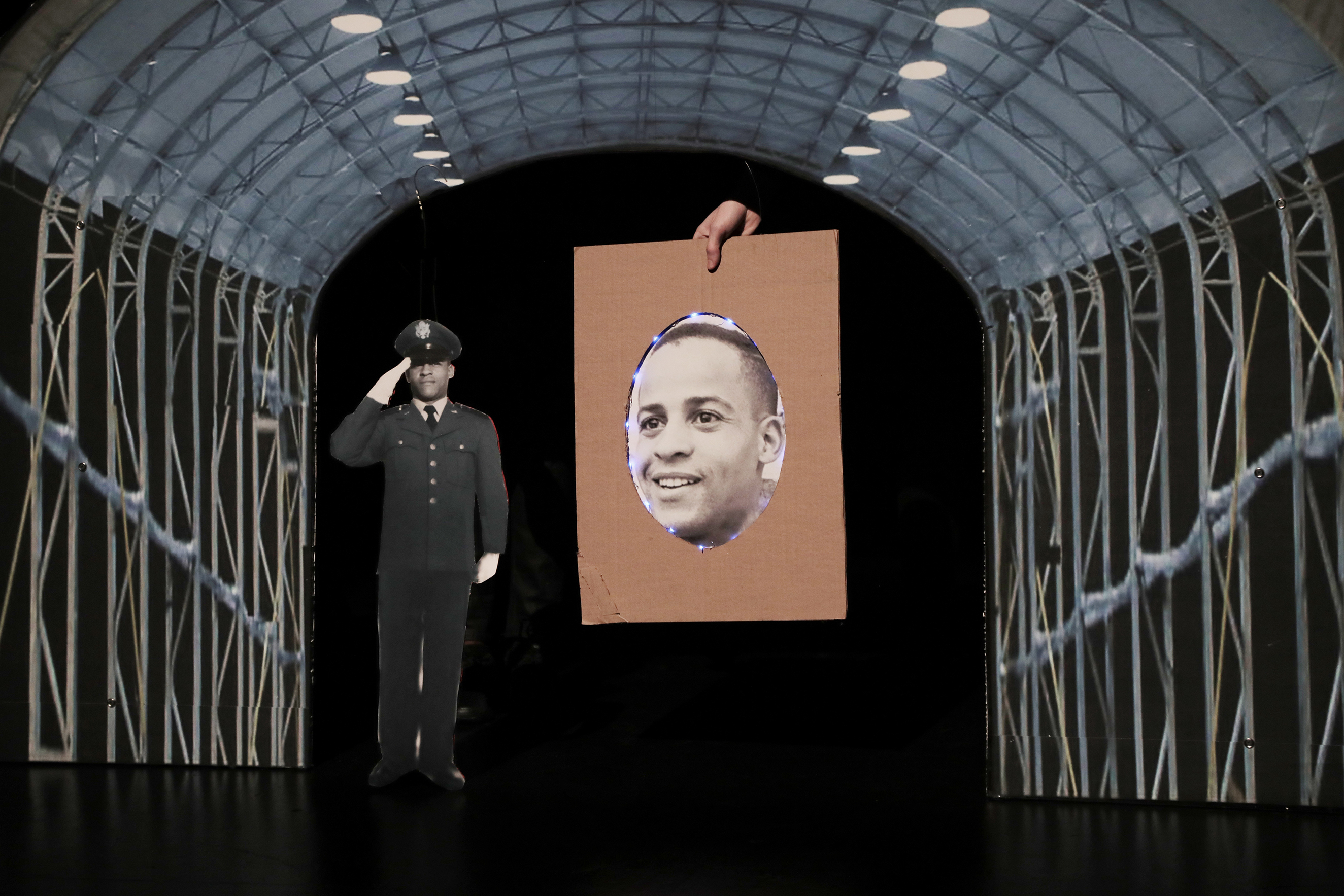 a man saluting next to a drawing of a face on a piece of cardboard