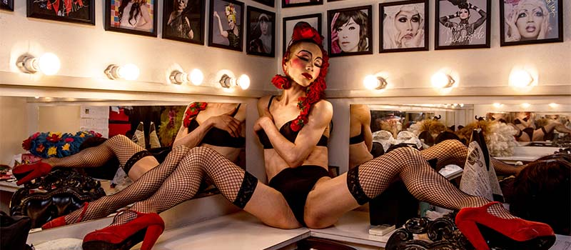 person wearing fishnets sitting on a dressing room counter