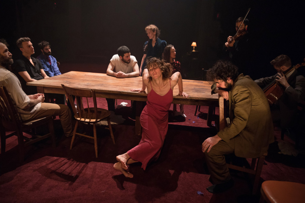 Production photo. a woman in a red dress leans on a table behind her. other performers and musicians are also at the table