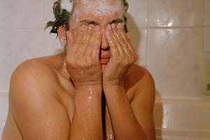 person sitting in a bathroom with suds on their head