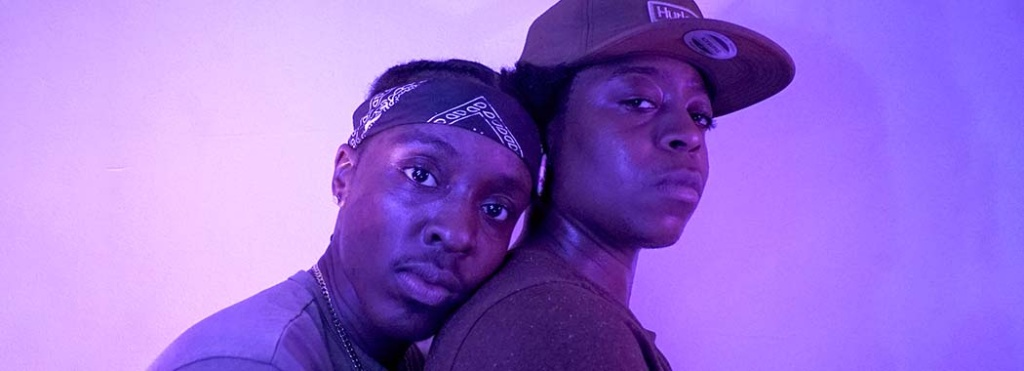 two people lit in purple light. one is holding the other from behind.