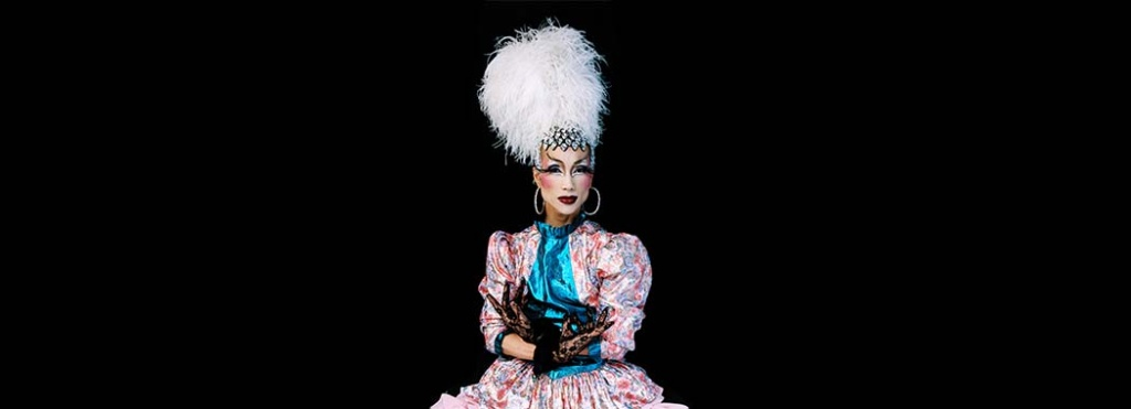 performer in a pink and blue dress with a tall, white, feathery hat
