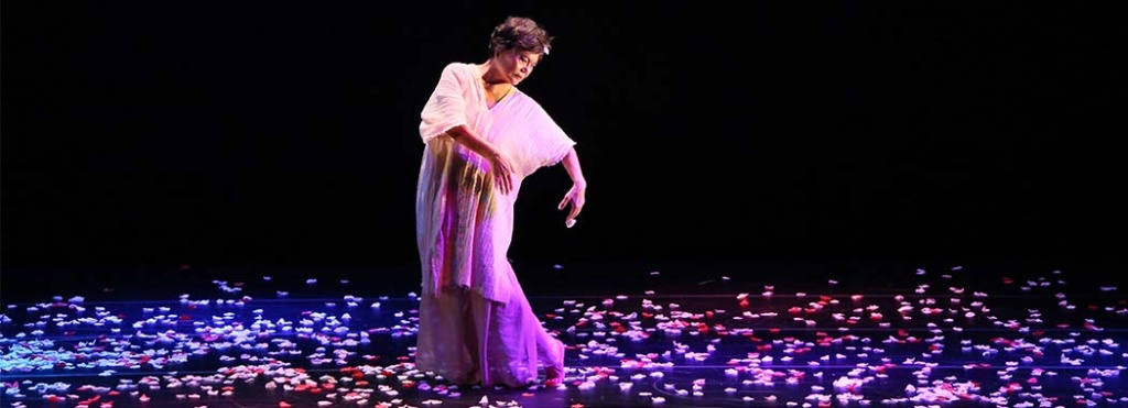 woman dancing on stage covered in small pieces of paper for mirror