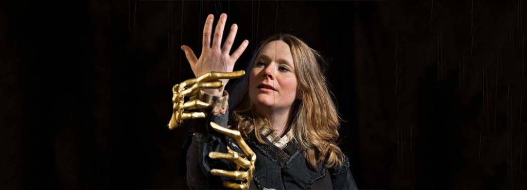 performer with golden hands looking at a human hands