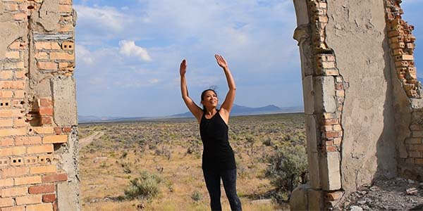 woman with her arms raised in the ruins of a building