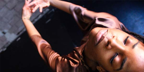 performer wearing brown with their eyes closed and arms outstretched