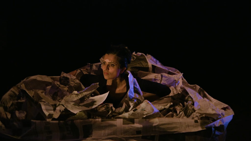 performer surrounded by paper