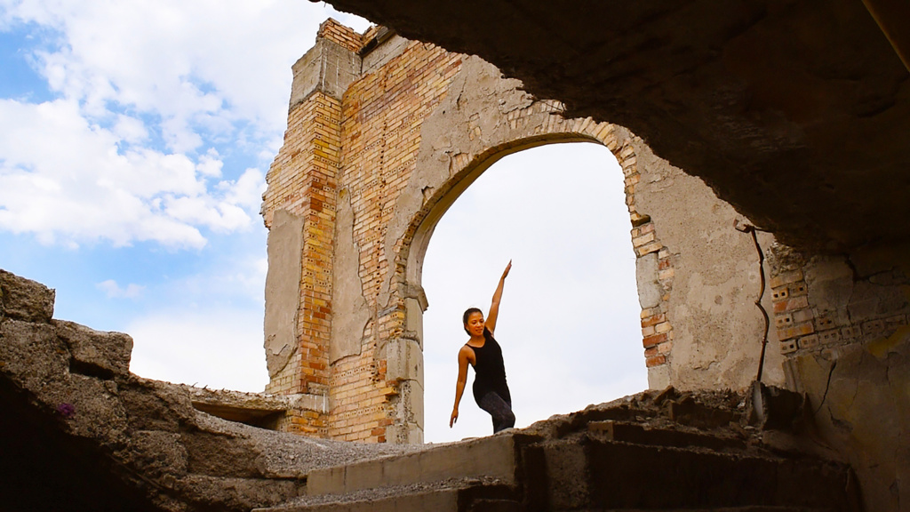 performer dancing in the ruins of a building