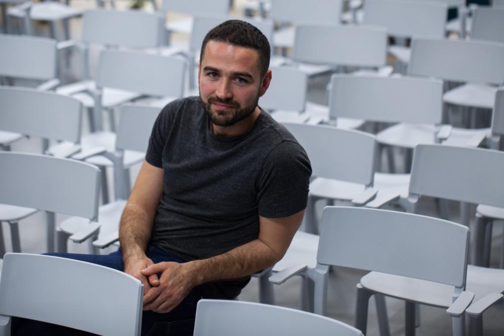 man sitting among white chairs