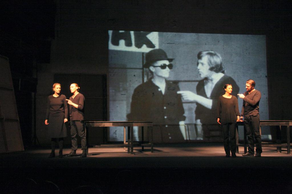 four performers wearing black onstage