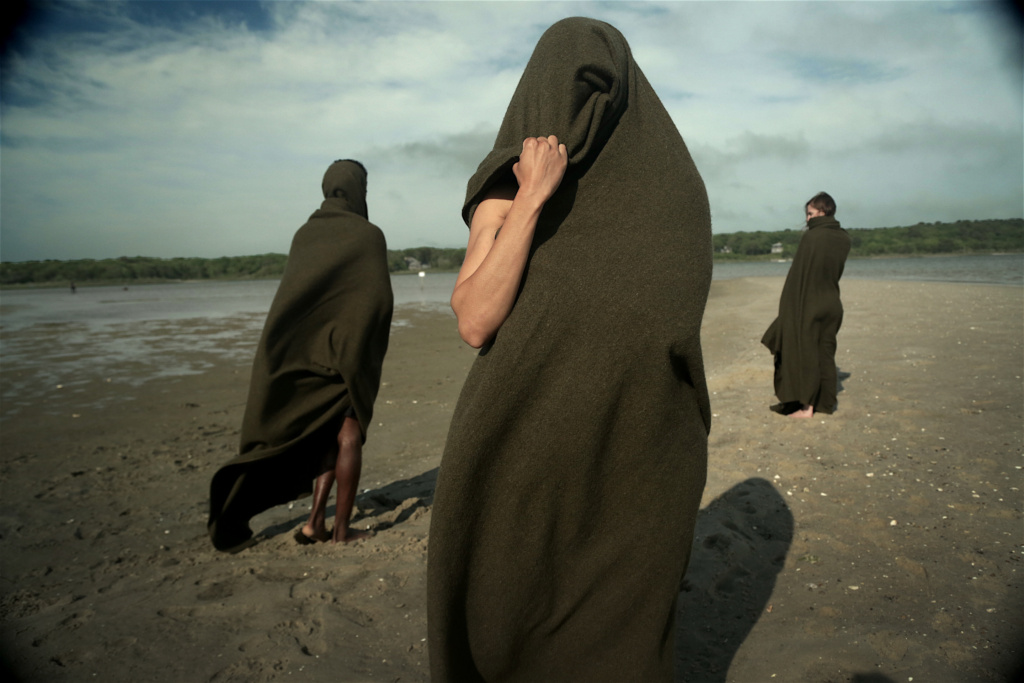 cloaked figures on the beach, one is facing the camera