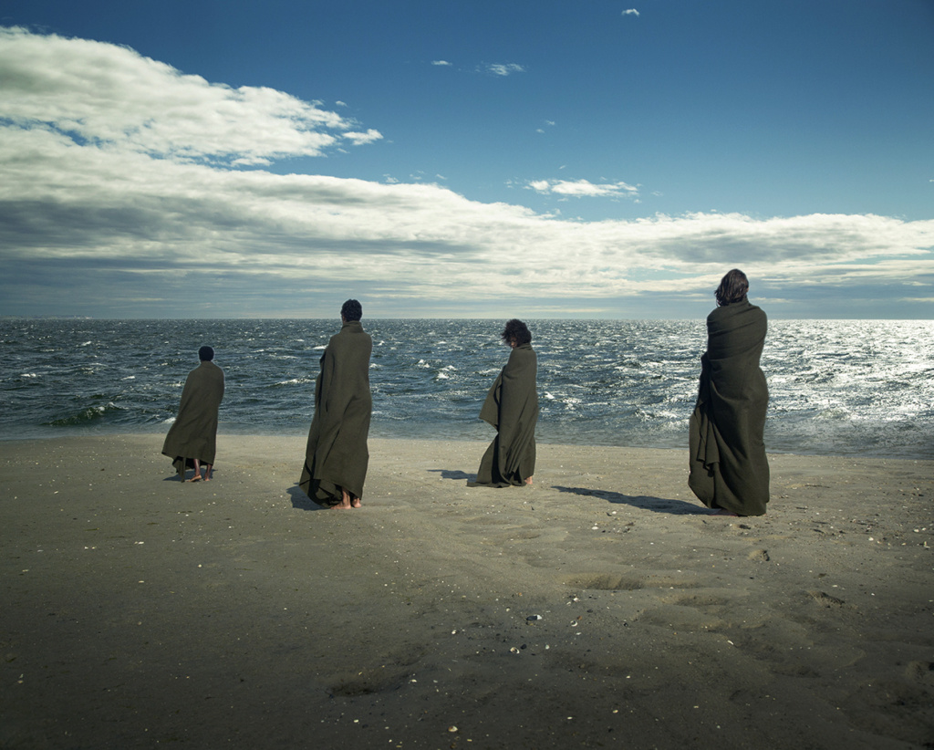 four cloaked people on a beach facing the ocean