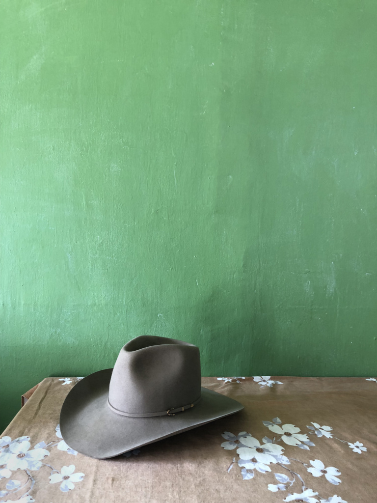 cowboy hat in front of a green wall