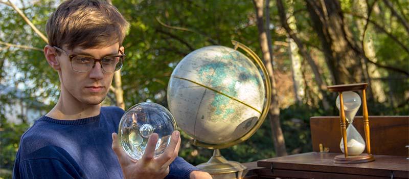 man looking at a glass globe