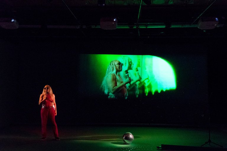 production photo of a performer standing in front of a green projection
