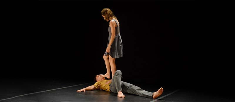 two performers onstage, one is laying on the floor