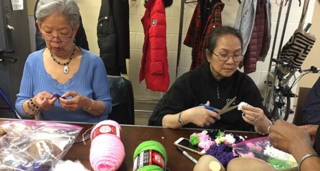 women making puppets at a table