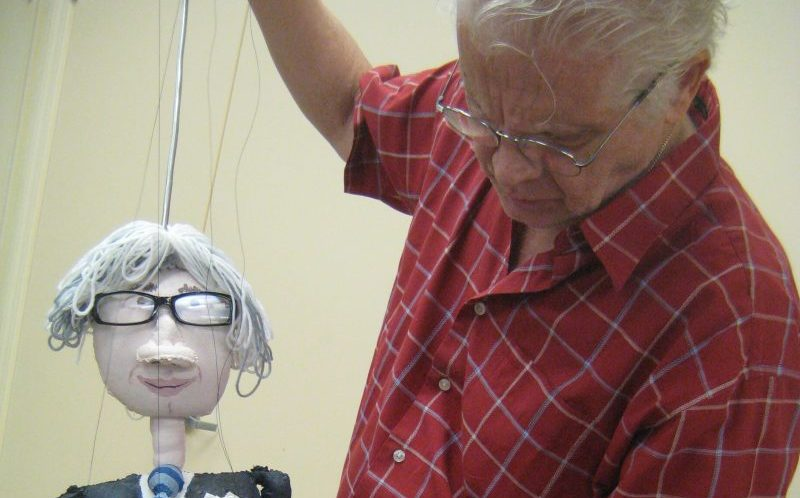 man holding a puppet on a string